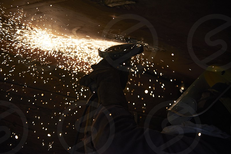 Welder hard at work at a shipyard underneath a large vessel with fire sparks flying around everywhere photo