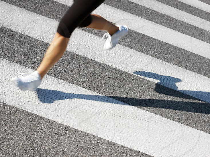 woman; running; fitness; runner; athlete; jogging; sport; cropped; one person; people; human legs; legs; Caucasian; 20s; 30s; female; young; adult; young adult; young woman; low section; sports clothing; footwear; shoes; shadow; outdoors; urban; urban scene; road; street; motion; motion blur; blurred motion; fast; speed; pedestrian; crossing; white; stripe; stripes; pedestrian crossing; asphalt; exercising; exercise; training; movement; healthy lifestyle; working out; wellness; copy space photo