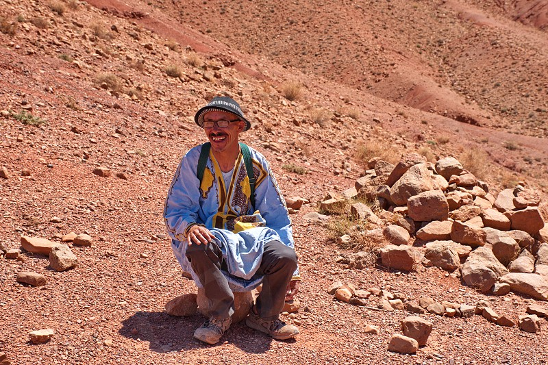 Old Berber sitting and resting in Morocco desert photo