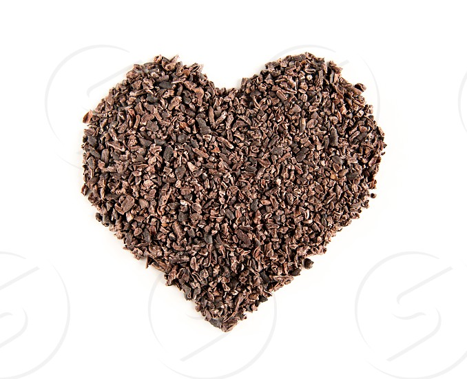 Dark cocoa nibbs in a shape of a heart on a white background. photo