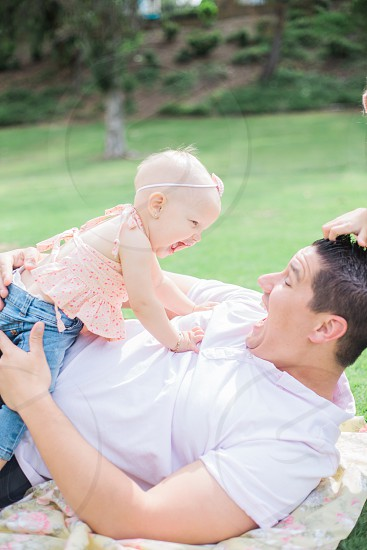 baby in pink halter top and blue denim pants laughing with man in white polo shirt laying outdoors photo