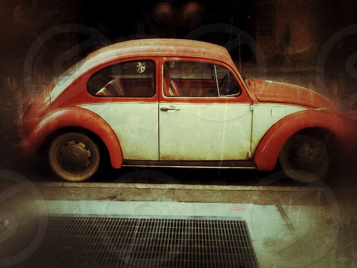 red and white volkswagen beetle parked on the sidewalk photo