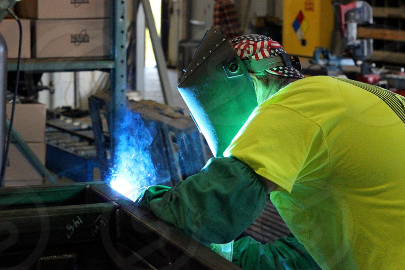 Work working worker weld welding labor man union green yellow hot bright hat cap job protection fire construction photo