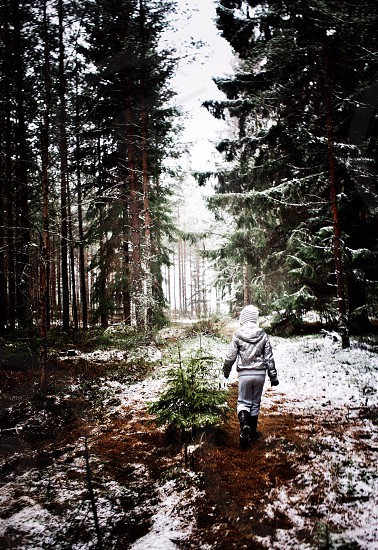 kid in white knit cap walking on the forest with snow photo
