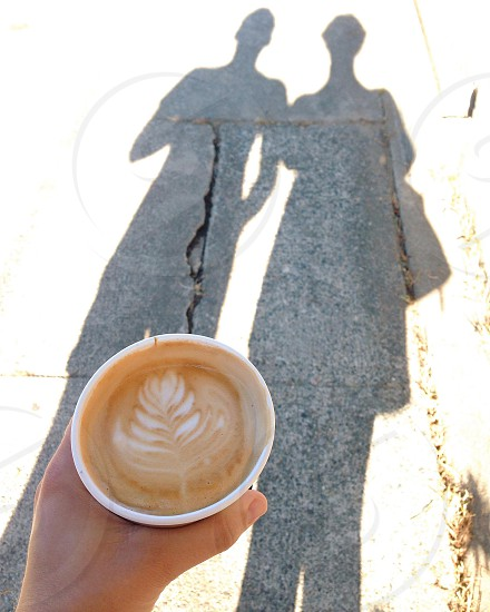 person holding a fully filled coffee cup photo