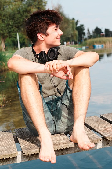 Young smiling boy sitting on jetty over the lake on sunny day in the summertime photo