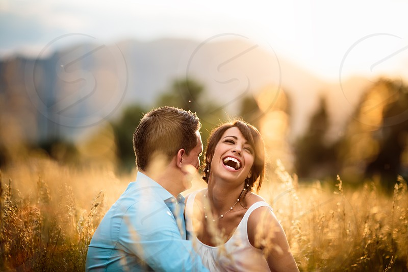 laughing woman and man sitting in gold field photo