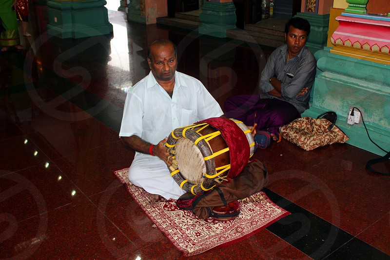 man in white thobe playing percussion instrument kneel on red and white rug photo