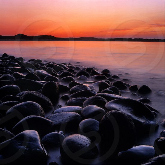 Sea scape shot at sunset with large round rocks in the foreground at Emblaton BayNorthumberland EnglandUK photo