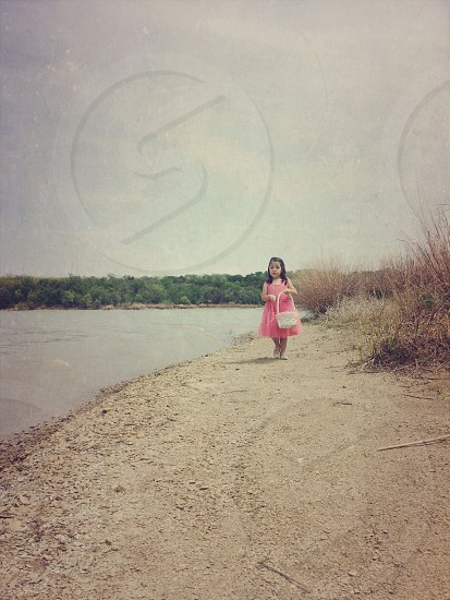 child in a pink dress beside the river photo