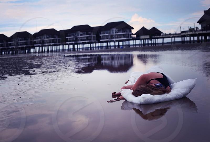 Girl lying on pillow in ocean sunset photo