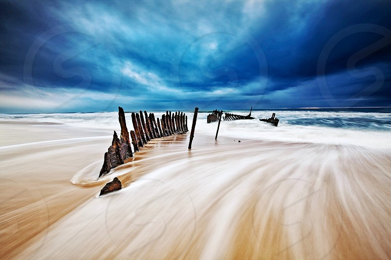 Linen filter used. Wreckage of SS Dicky with a moody storm brewing off Dicky beach Sunshine Coast Queensland. photo