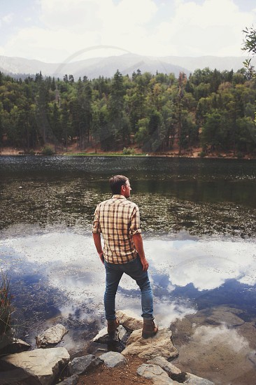 man in brown and beige checkered button down shirt and blue denim jeans photo