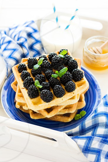 Belgian waffles with blackberries honey and milk photo