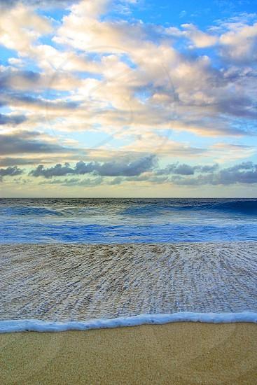 blue seashore behind beige sands under white blue sky during daytime photo