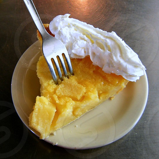 Chess pie with fork and whipped cream on beige plate on aluminum tabletop photo