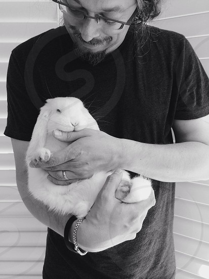 man in black t shirt holding a white bunny rabbit photo