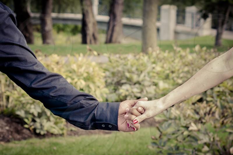 Couple intimately holding hands. photo