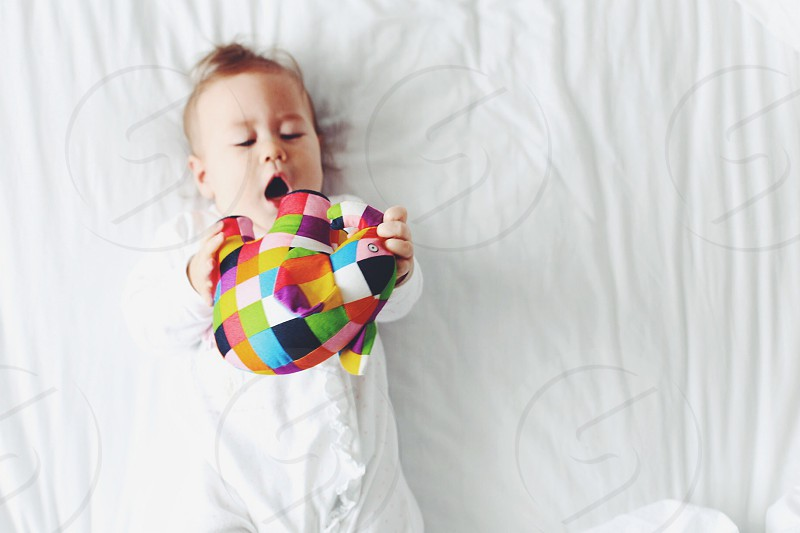 baby's holding a multicolored animal flush photo