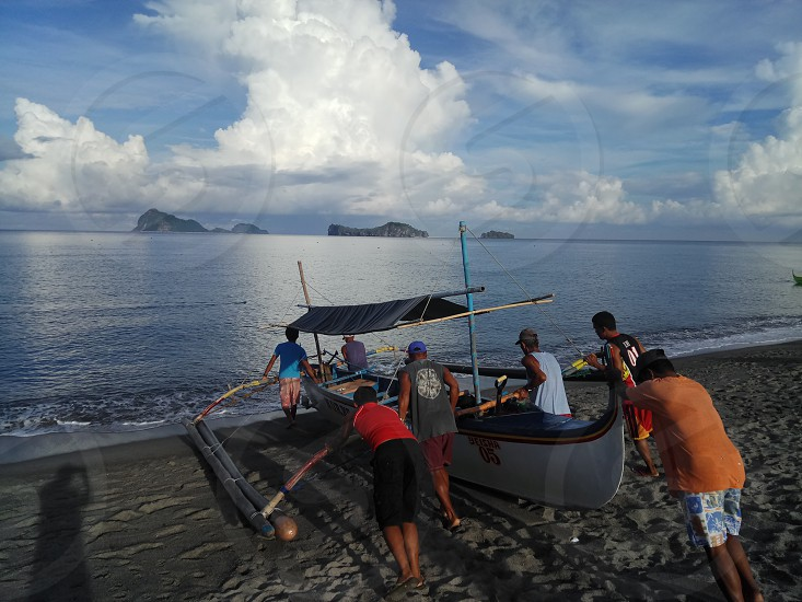 people pushing boat towards water under cloudy sky photo