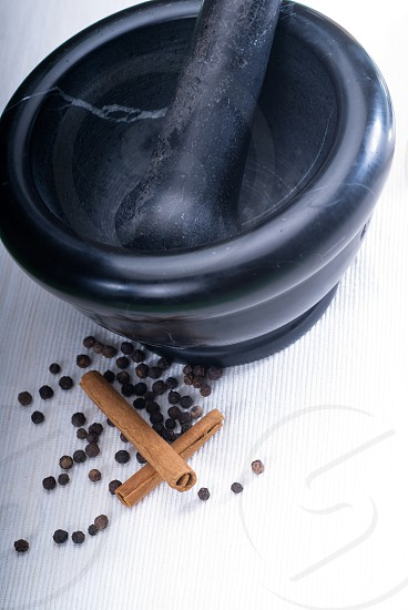 black stone mortar and pestel with cinnamon and pepper photo