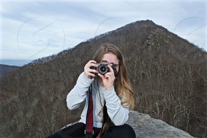 woman wearing gray long-sleeved top sitting on rock while taking a photo using black DSLR camera during daytime photo