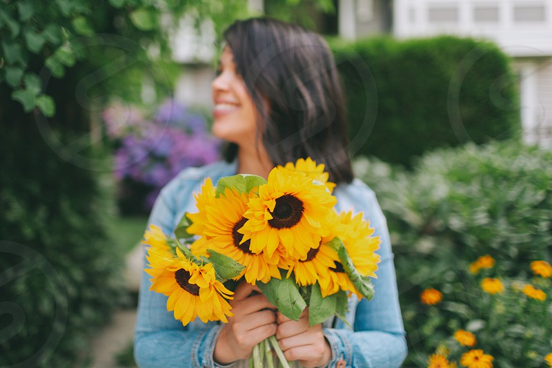 A woman holding a bouquet of sunflowers. photo