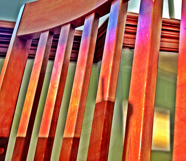 Seat back of a wooden chair bathed in evening sunlight. photo