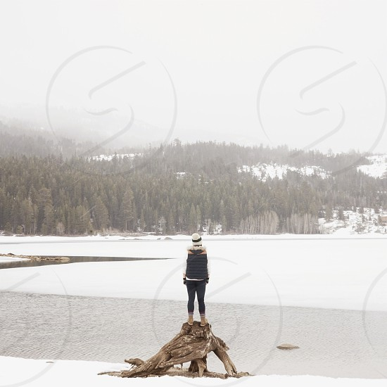 woman in red and white striped beanie standing on brown drift wood photo