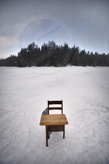 An old wooden school desk on a frozen lake while it is snowing. photo