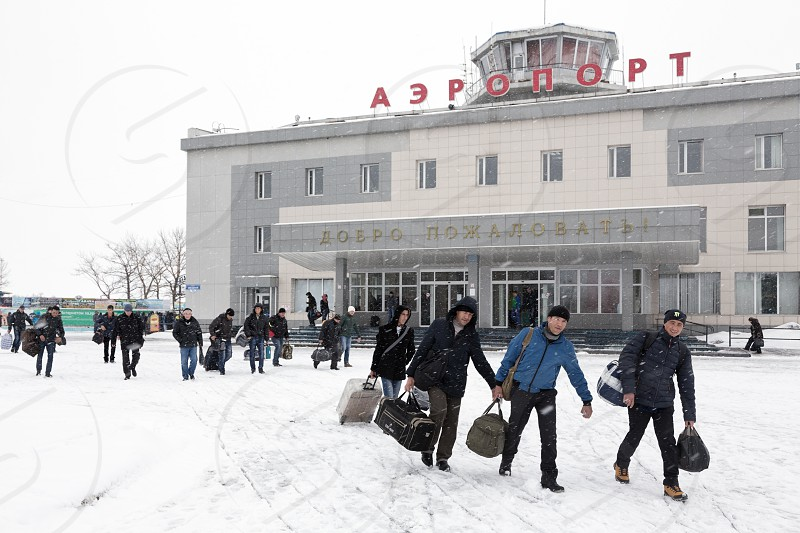 PETROPAVLOVSK-KAMCHATSKY KAMCHATKA RUSSIA - MARCH 19 2015: Winter view of the airport terminal Petropavlovsk-Kamchatsky (Yelizovo airport) and the station square with the passengers with baggage. photo
