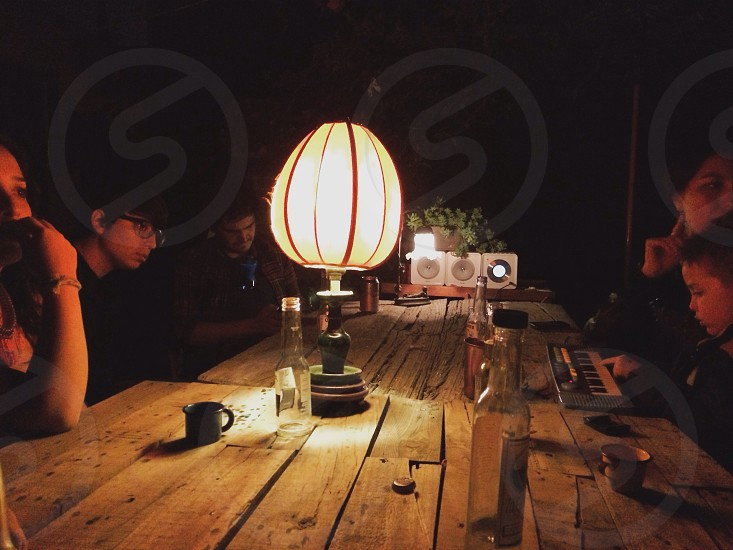 people sitting at wood table with lamp photo