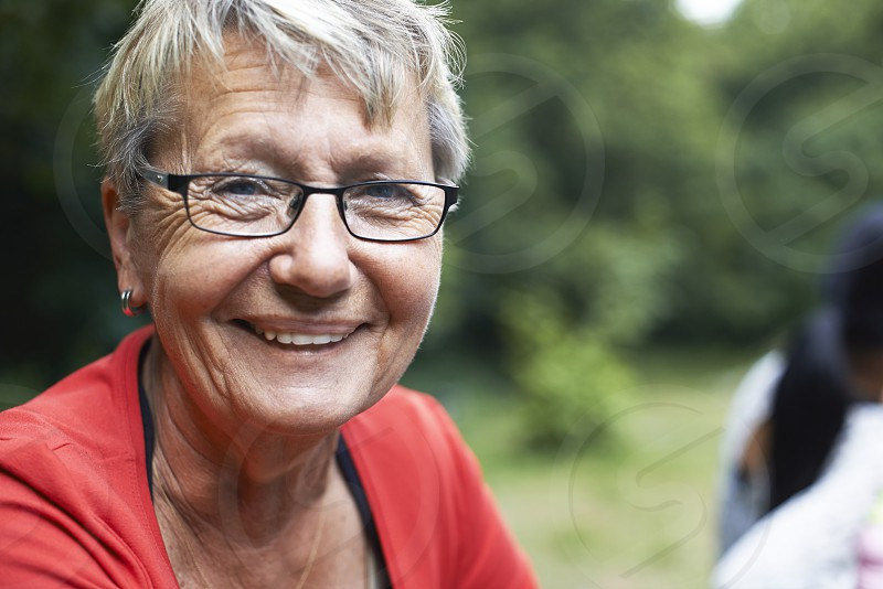 Portrait of a elderly caucasian woman smiling into camera in summer sunshine photo