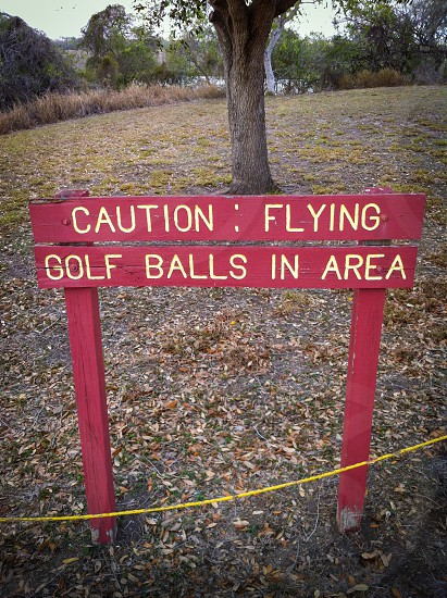 caution flying golf balls in area signage photo