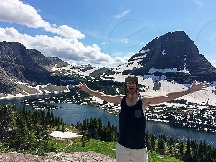 Man arms raised in Montana with gorgeous Hidden lake and Bearhat mountain behind him. photo