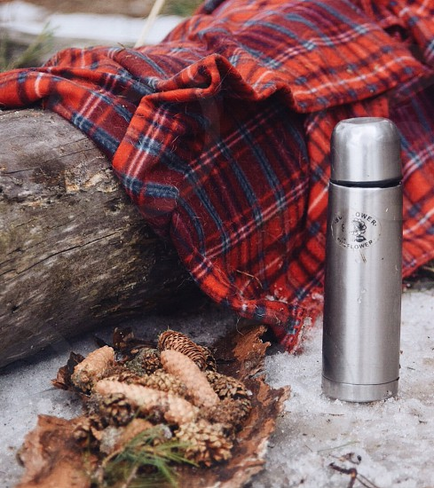 stainless steel vacuum flask beside red and blue plaid mat photo