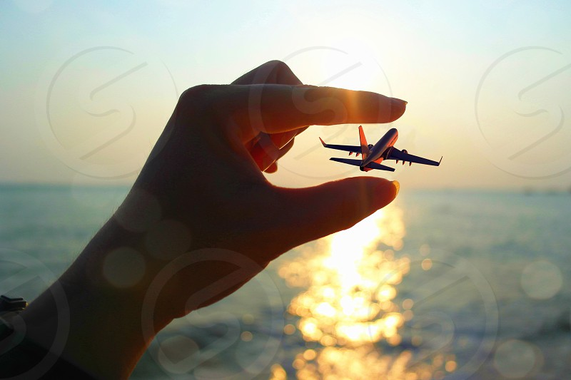 person measuring the length of the air plane flying above body of water during day time photo