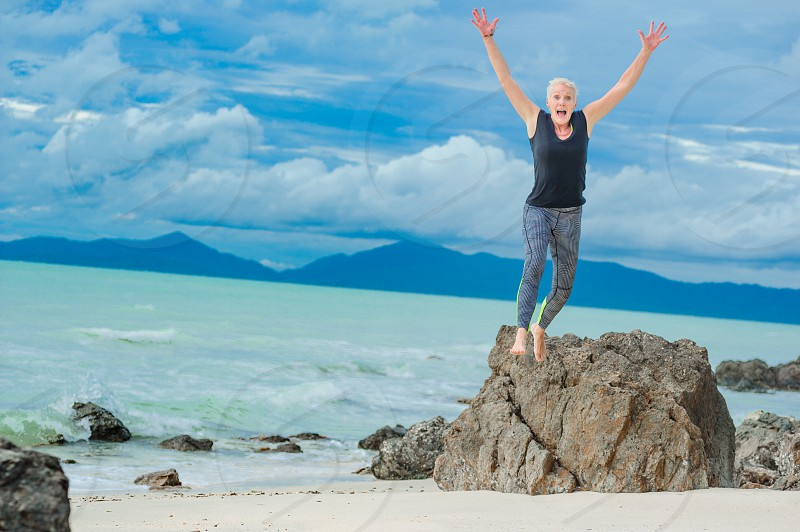 Beautiful mature aged woman jumps and having fun on a desert tropical beach. photo