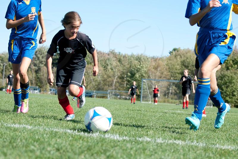 children playing soccer on green grass field photo