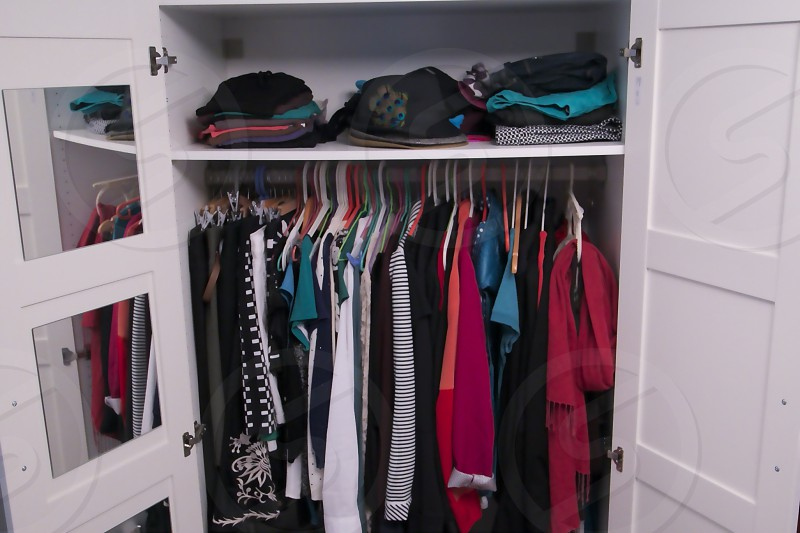 open double-door white wood closet with hanging shirts and upper closet photo