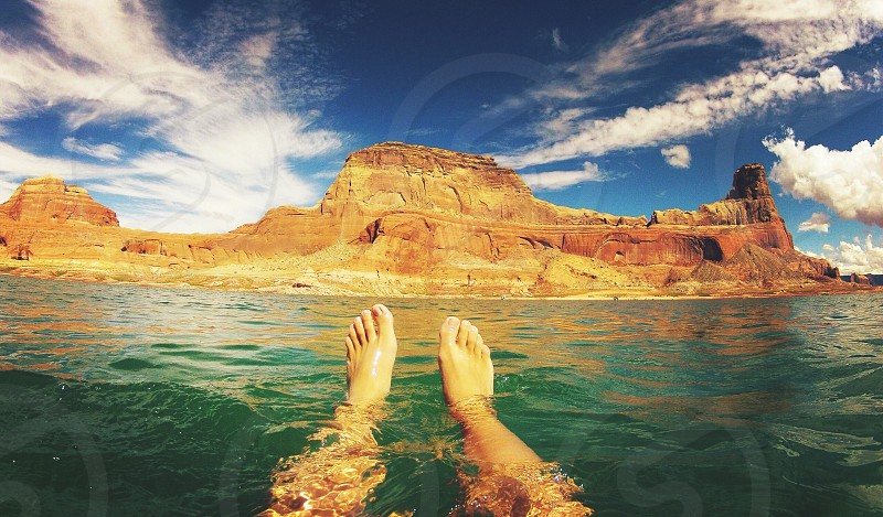 person's feet in green water near brown rocky mountain under white cloudy blue sky photo