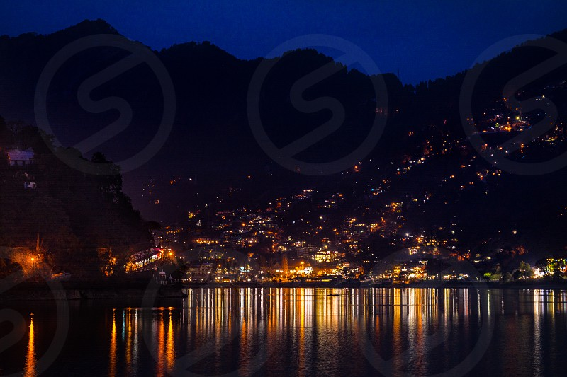 A town in himalayan range called Nainital at an elevation of roughly 2000m. It was a typical night in winter chilly weather with beautiful soft reflections of town lights into the lake water. photo