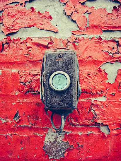 black mounted call button mounted to a red peeling paint wall photo