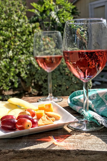Pair of wine glasses with rose wine in an outdoor setting photo