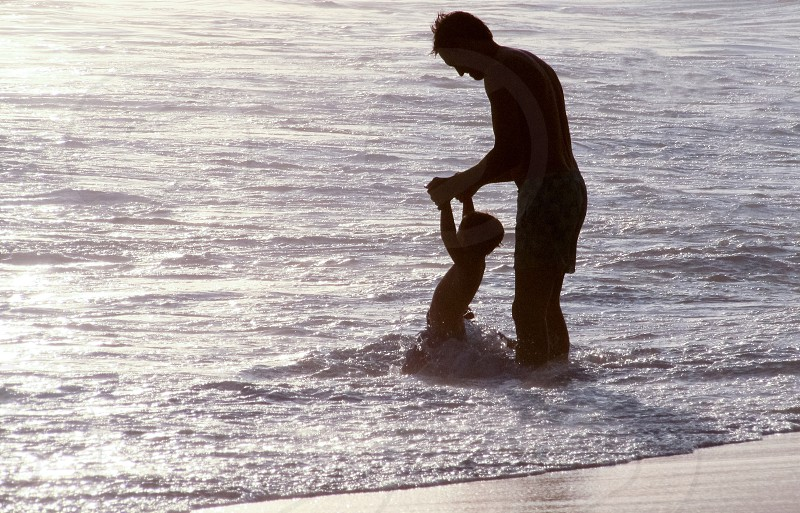 silhouette of man holding child's hands on blue ocean water during daytime photo