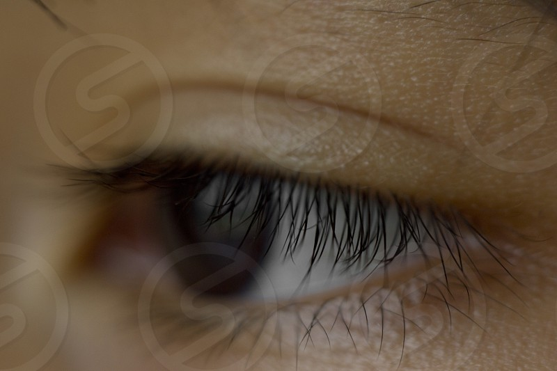 Macro close up of young Asian boy deep black eye in almond shape photo