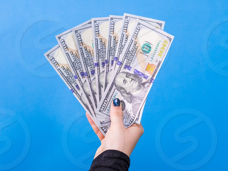 Woman hand with dollars isolated on blue background photo