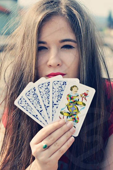Young teenager girl holding tarocchi cards with the lucky card turned around. photo