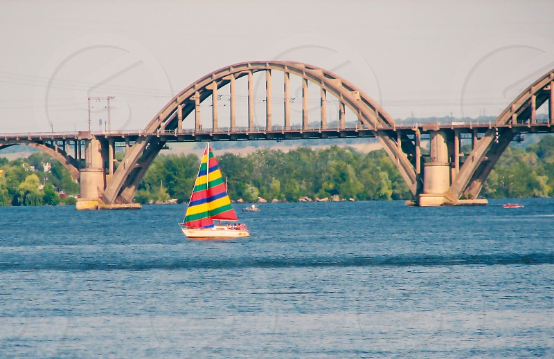 white red green yellow and blue striped sailboat sailing on blue river near brown arch bridge during daytime photo