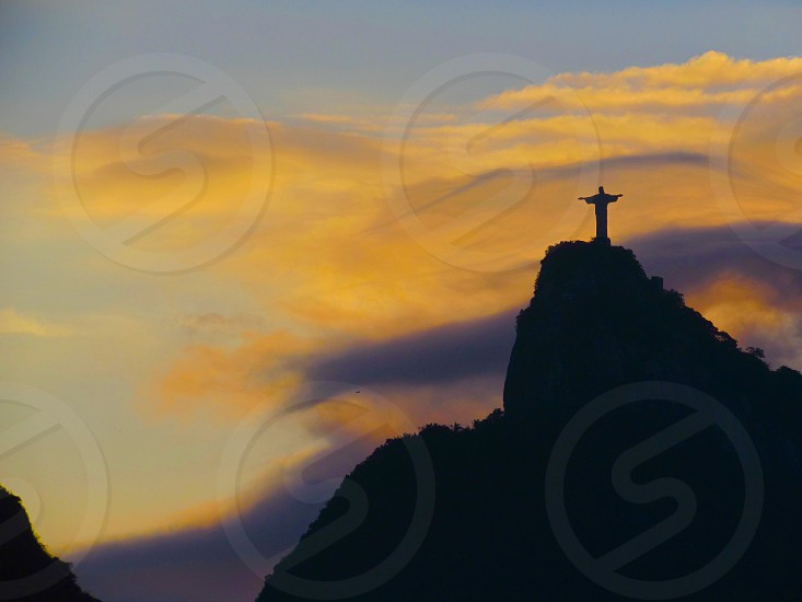 silhouette of christ the redeemer on top of sugarloaf mountain under grey and yellow clouds photo